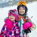 Portrait of two little girl in  ski helmet and mask in winter resort